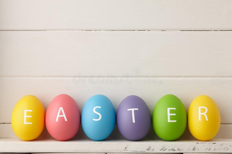 Målade ägg med bokstäver som ordnas i ordpåsk fotografering för bildbyråer