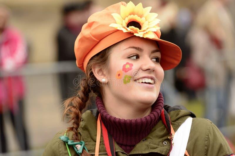Målade blommor på kind av den trevliga utklädda kvinnan på karnevalPA arkivbilder