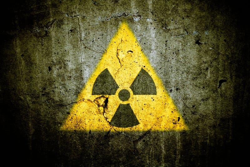 Målade det varnande symbolet för radioaktiv atom- kärn- fara för joniseringsutstrålning i triangulär form den massiva spruckna be arkivbilder