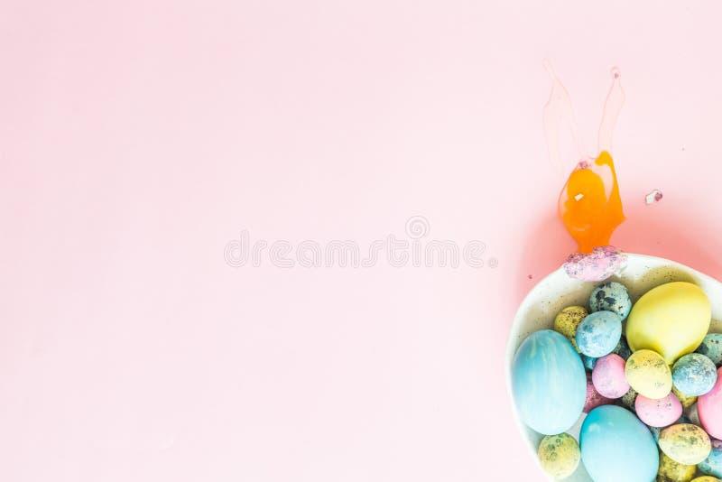 Målade easter ägg i den vita plattan och ett brutna ägget som ligger på rosa bakgrund Top beskådar Lekmanna- lägenhet placera tex royaltyfri fotografi