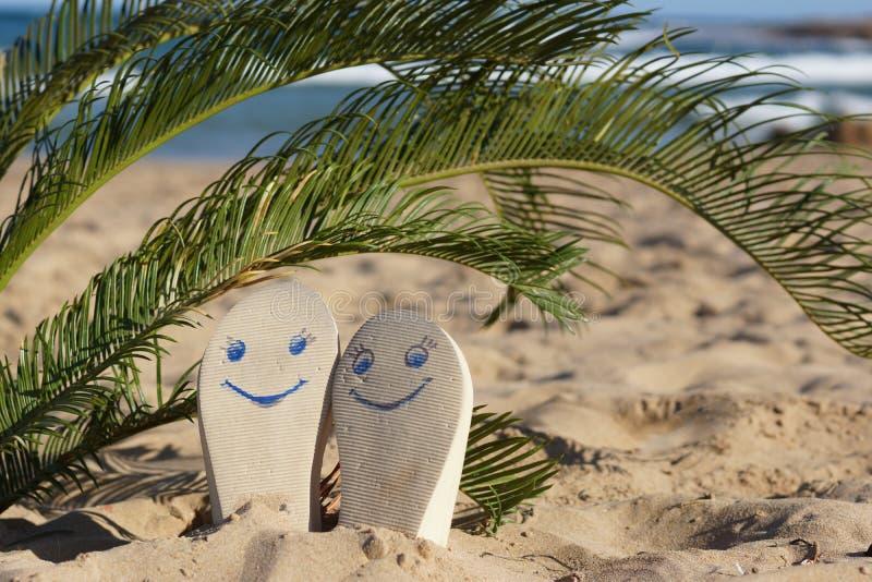 Målade emoticons på strandhäftklammermatare på sand under en palmträd vid havet i sommar arkivbilder