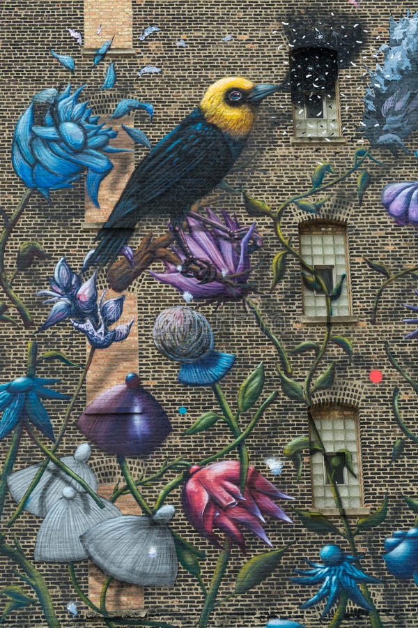 Målade fåglar på tegelstenväggen arkivfoton