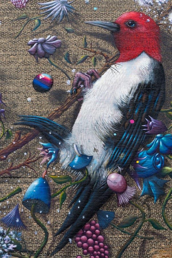 Målade fåglar på tegelstenväggen arkivfoto
