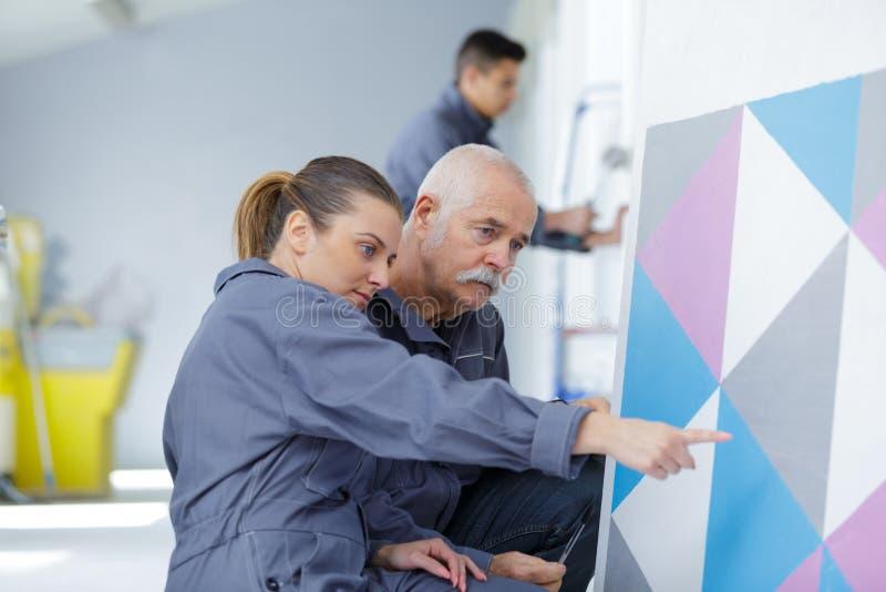 Målare med lärlingen i utbildande rum arkivbild