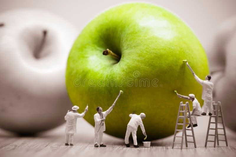Målare som färgar det gröna äpplet Storen specificerar! arkivfoto