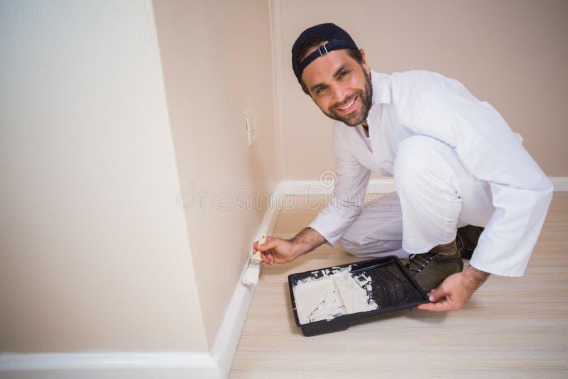 Målare som målar de vita väggarna arkivfoto
