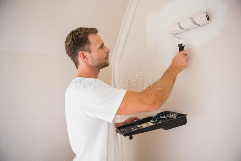 Målare som målar de vita väggarna arkivbild