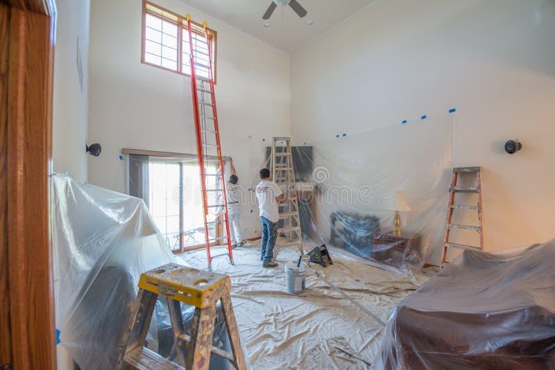 Målare som målar ett hus arkivbild