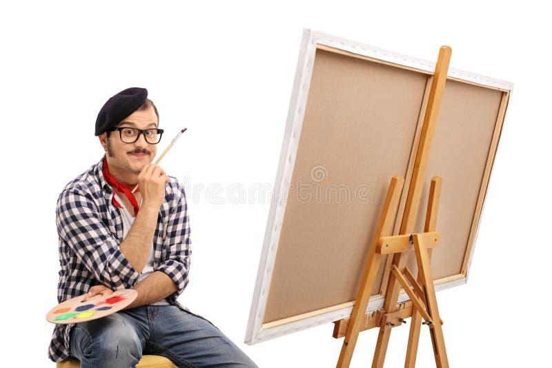 Målare som poserar bredvid en kanfas och beskåda royaltyfri foto