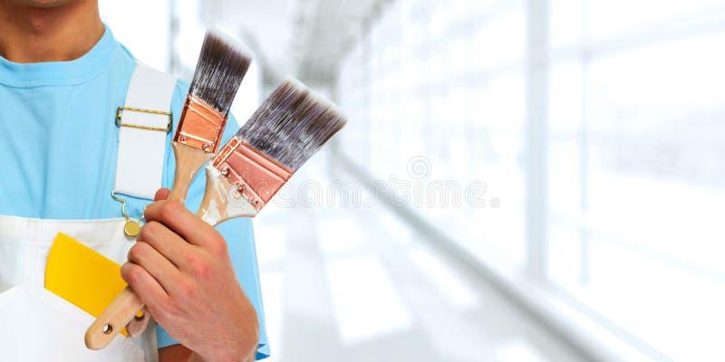 Målarehand med målningborsten royaltyfri bild