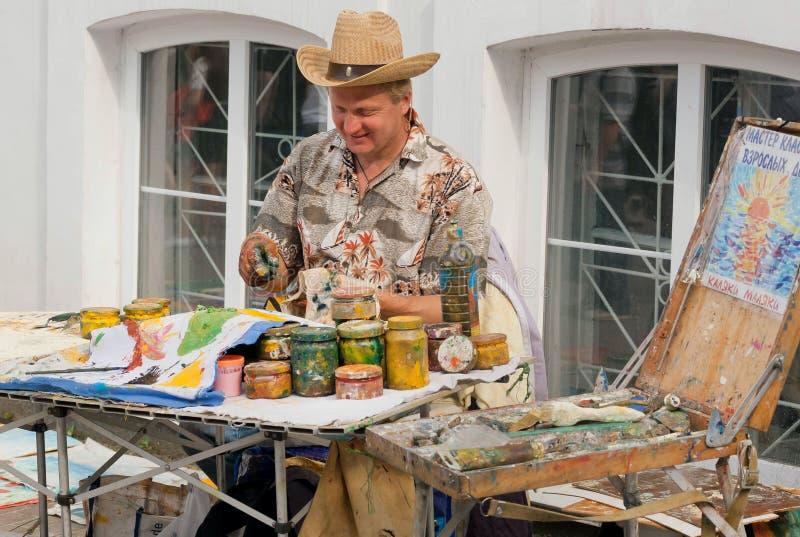 Målarekonstnär som arbetar med målarfärger på gatan för deras egen advertizing arkivbilder