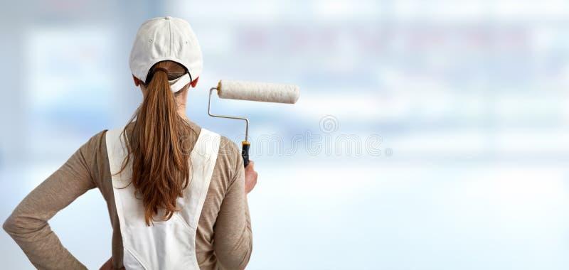 Målarekvinna med målningrullen fotografering för bildbyråer