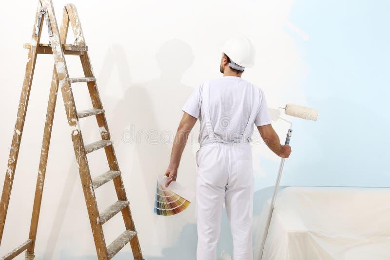 Målareman på arbete med en målarfärgrulle och färgprövkopior arkivfoto