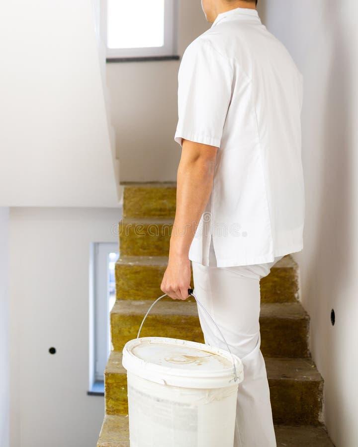 Målareman som arbetar i vita väggar för en husmålning royaltyfri foto