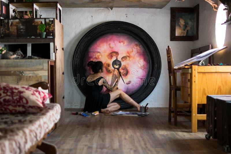 Målaren avslutar hennes stora målning som ligger på golvet arkivfoton