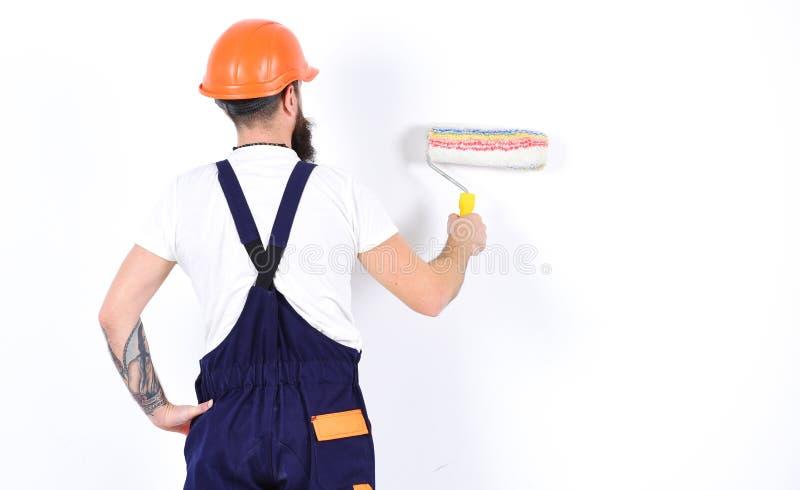 Målaren dekoratören, byggnadsarbetare arbetar framme av den vita väggen, rymmer målarfärgrullen, vit bakgrund renovering arkivbild