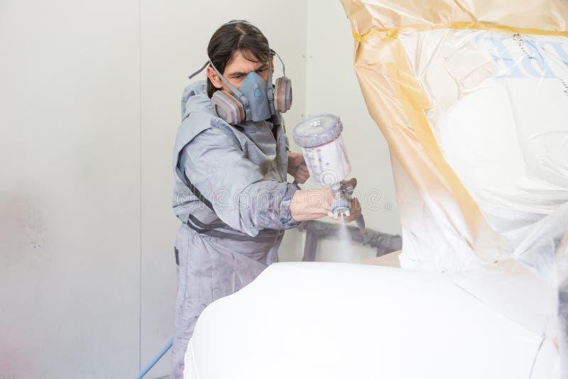 Målaren för bilkroppen som besprutar målarfärg på karosseri, särar royaltyfri bild