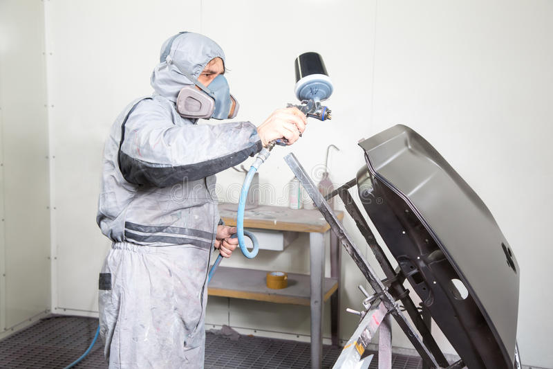 Målaren för bilkroppen som besprutar målarfärg på karosseri, särar arkivfoton
