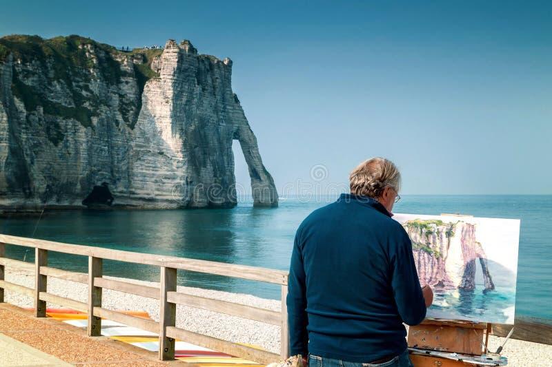 Målaren målar de berömda vita klipporna av Etretat royaltyfri foto