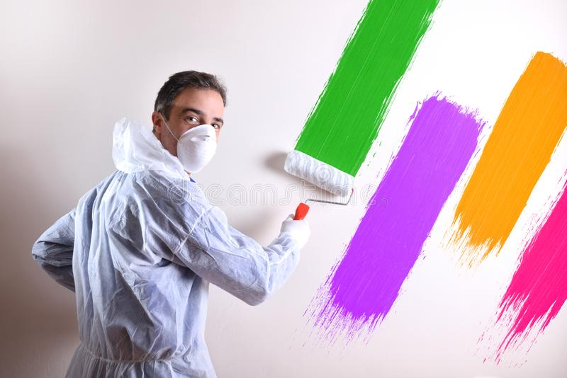 Målaren som vänder med overals, och väggen målade med fyra färger royaltyfria bilder
