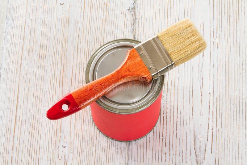Målarfärg kan borsta, den vita Wood golvplankan för röd färg royaltyfri bild