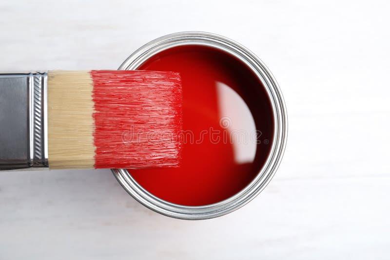 Målarfärg kan och borsten på träbakgrund arkivfoton
