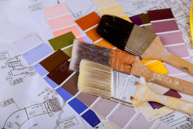 Målarfärg med målarfärgborsten och på färg tar prov kortet royaltyfri bild