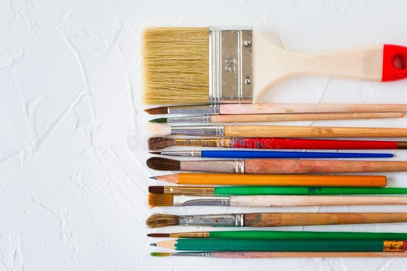 Målarfärgborstar av olika format och blyertspennor på vit texturbakgrund Konst- och utbildningsobjekt fotografering för bildbyråer