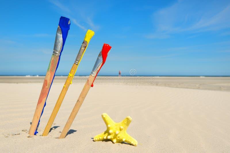 Målarfärgborstar på stranden fotografering för bildbyråer