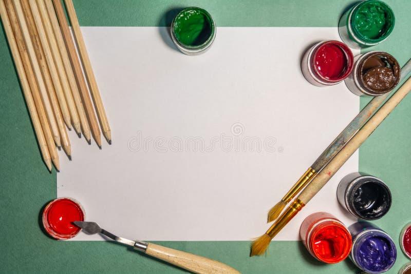 Målarfärger, borstar och blyertspennor på ljus bakgrund arkivbilder