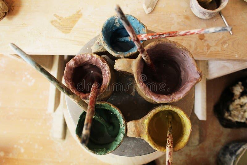 Målarfärger för att måla lera i krus royaltyfri foto