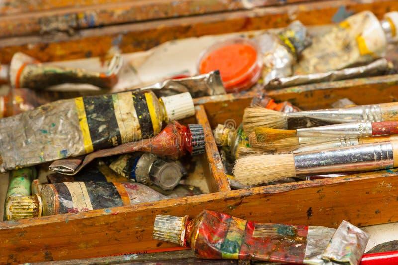 Målarfärger och borstekonsttillförsel i målningstudio arkivbild