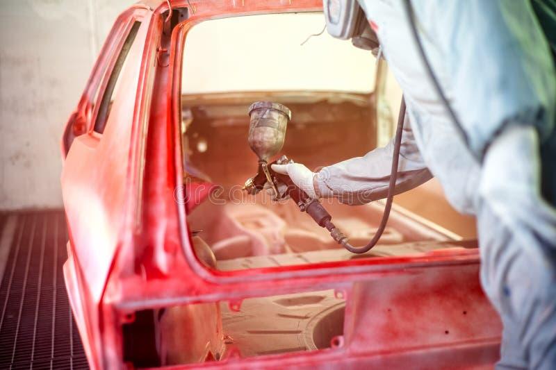 Målarfärgtekniker som arbetar på den röda bilen arkivbilder