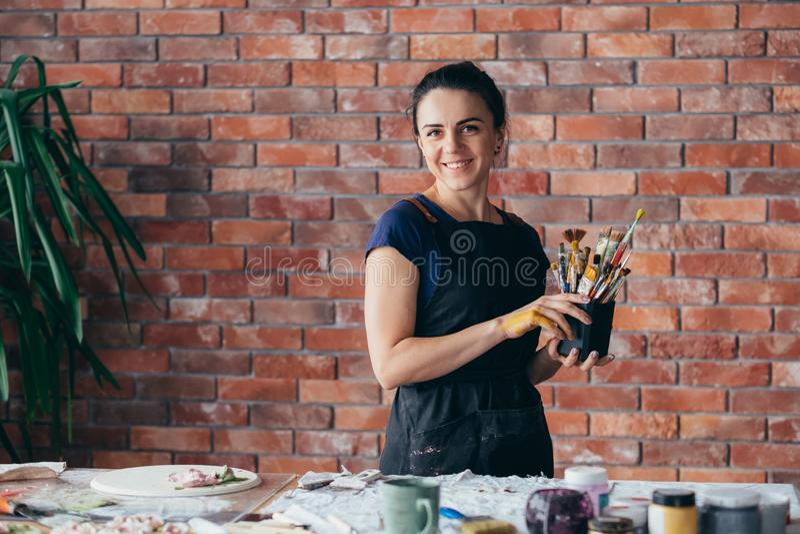 Målarpenslar för konstnär för arbete för kvinna för konststudio idérika arkivbilder