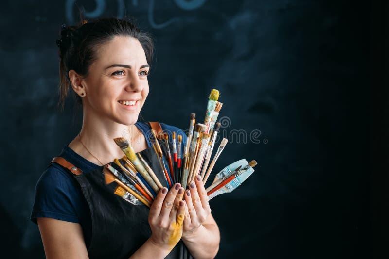Målarpenslar för ung kvinna för konstnärtillförselkonstverk arkivfoton