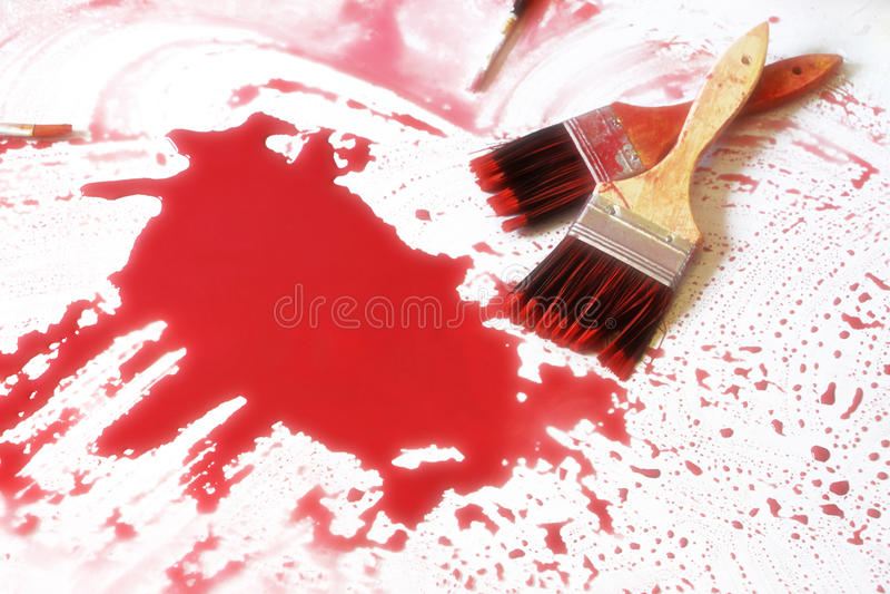Målarpenslar och den röda färgen arkivbild