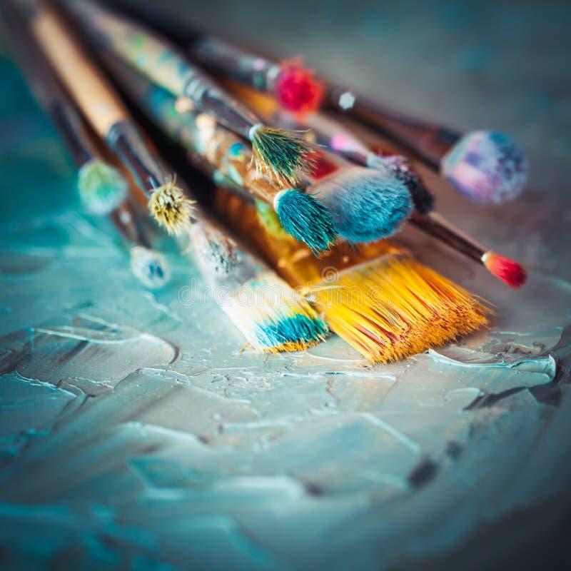 Målarpenslar på konstnärkanfas som täckas med olje- målarfärger fotografering för bildbyråer