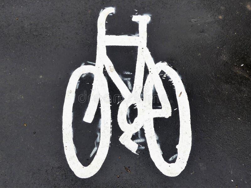 Målat cykeltecken på asfalttrottoar royaltyfria bilder