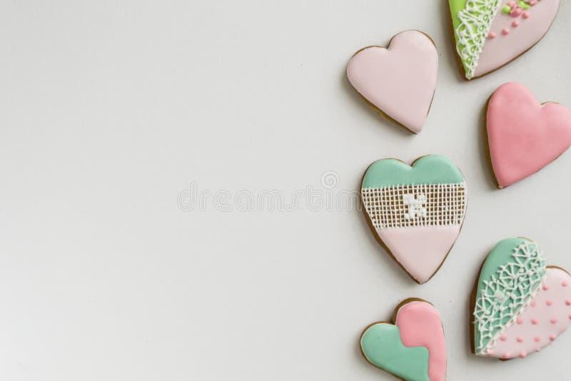 Målat rosa och färgat, ingefära och honungkakor och kakor I formen av en hjärta på en ljus träbakgrund royaltyfria foton