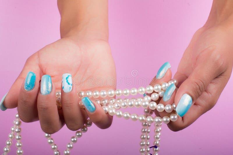 Målat spikar och pryder med pärlor royaltyfri fotografi