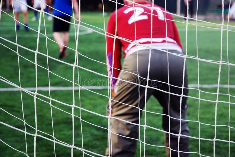 Målet förtjänar bak målvakt i röd likformig Alla spelar fotboll royaltyfria bilder