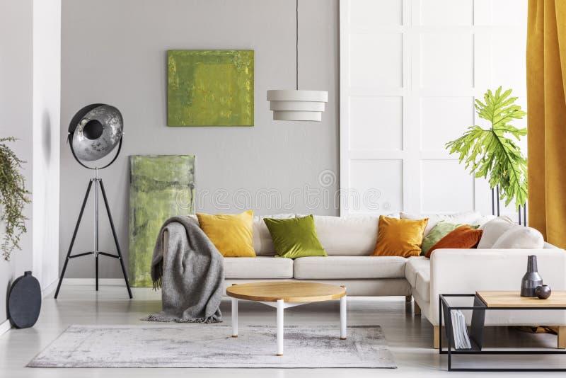 Målningar på väggen och den industriella lampan i hörnet av elegant vardagsrum som är inre med guld- limefruktbrytningar, verklig arkivbilder