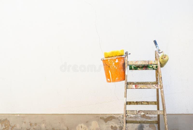 Målningtillbehör på en stege framme av en tom yttre husvägg royaltyfri foto