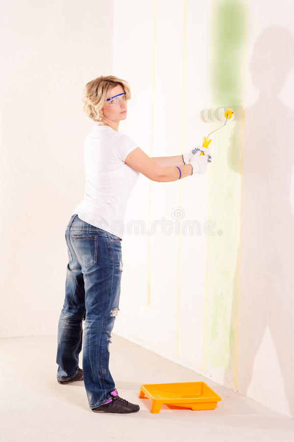 Målningvägg för ung kvinna inomhus royaltyfria foton