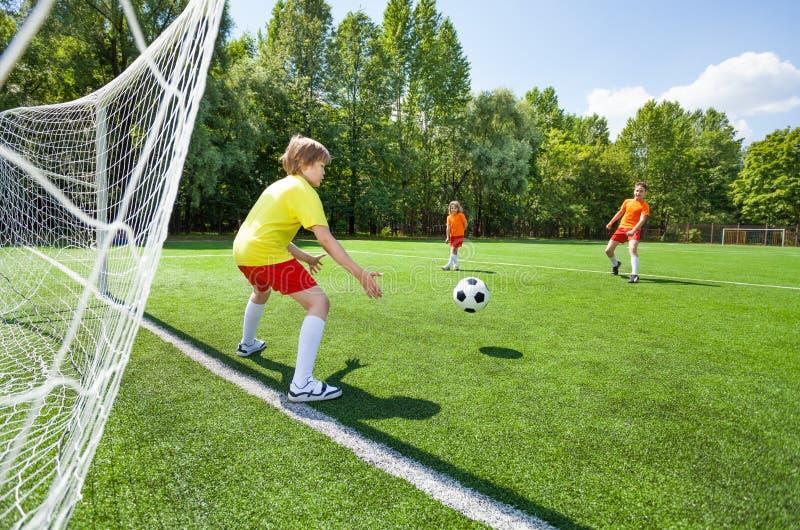 Målvaktförsök att fånga den kastade fotbollen arkivfoto