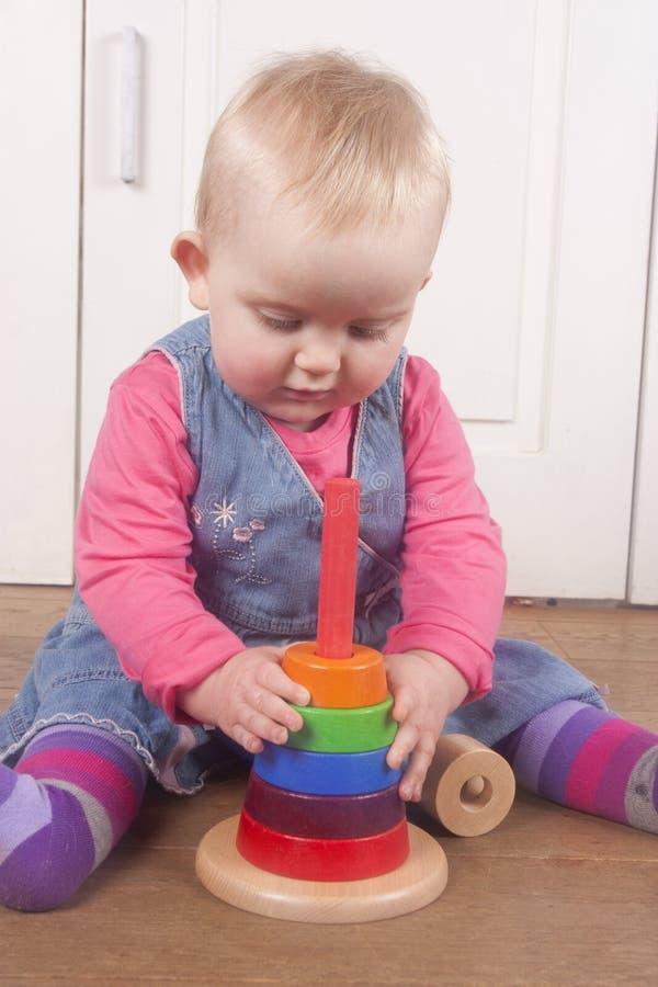 18 månad gammalt babby spela med träleksaken arkivbild