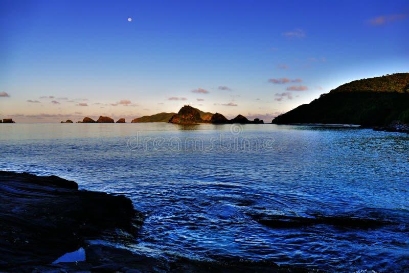 Måne fortfarande ovanför havet precis för soluppgång, Zamami, Japan royaltyfri foto