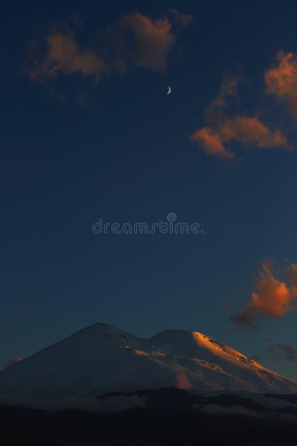 Måne i molnen ovanför maxima av Mount Elbrus under solnedgång arkivbilder