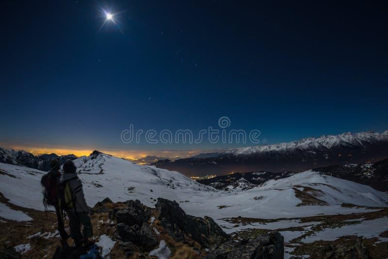 Måne och stjärnklar himmel, snö på fjällängarna, fisheyelins Orion Constellation Betelgeuse och Sirio Suddiga två fotvandrare l f royaltyfria foton