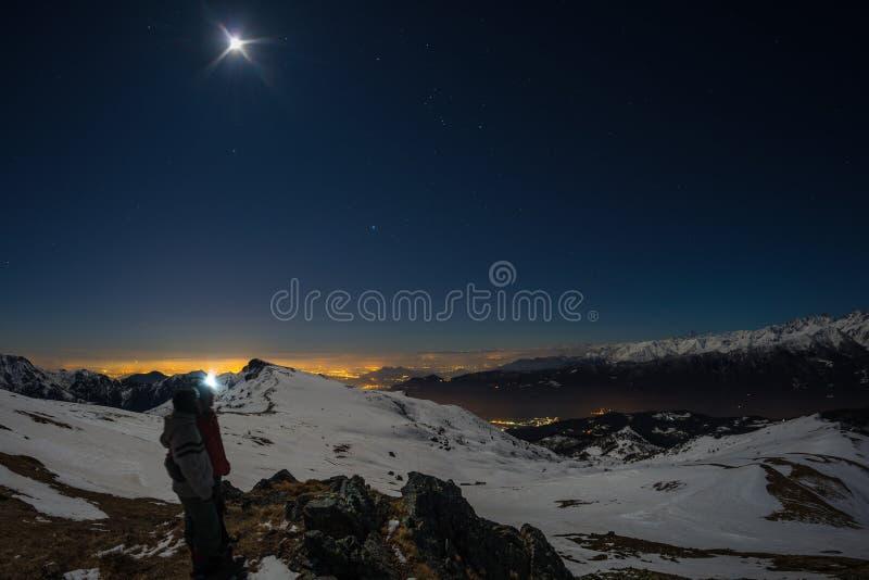 Måne och stjärnklar himmel, snö på fjällängarna, fisheyelins Orion Constellation Betelgeuse och Sirio Suddiga två fotvandrare l f arkivfoton